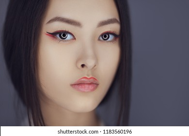 Serious asian beauty woman skin care close-up. Beautiful young girl with perfect skin face looking at camera. Isolated on gray background. Tender sensual mixed race Asian Caucasian female in studio