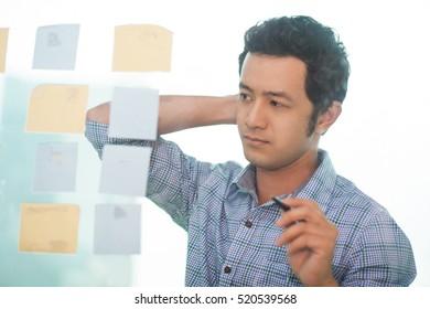 Serious Asian businessman looking at adhesive notes