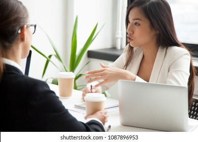 Serious asian businesswoman discussing project or brainstorming talking working with colleagues at meeting, millennial chinese manager making offer, explaining new idea to partners during negotiation