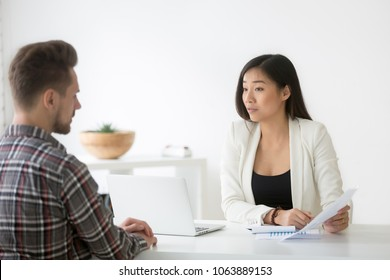 Serious asian businesswoman executive scolding employee holding document report dissatisfied with work results, skeptical unconvinced chinese hr manager asking questions about cv at bad job interview