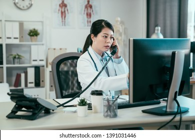 Serious asian female doctor on phone in office. young japanese woman medical worker in clinic hospital connecting with nurse on telephone call checking patient situation of surgery on computer screen
