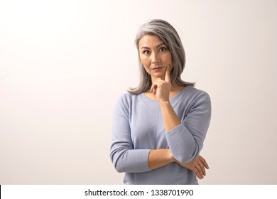 Serious Asian Woman Is Touching Her Chin With Pointing Finger. Horizontal Shot Of Beautiful Mature Woman Propping Her Chin On Her Hand.