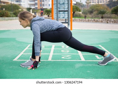 Serious athlete stretching hip muscles on outdoor playground. Sporty young woman warming up to start training. Warmup concept