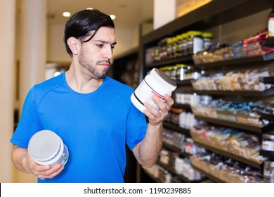 Serious athletic man attentevely looking sport dietary nutrition  in sport shop