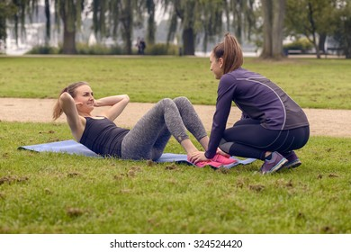 Serious Athletic Woman looking at her friend While Doing Curl Up Exercises at the Park