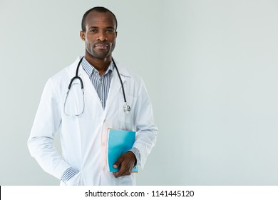 Serious attitude. Concentrated professional doctor holding patients notes against white background