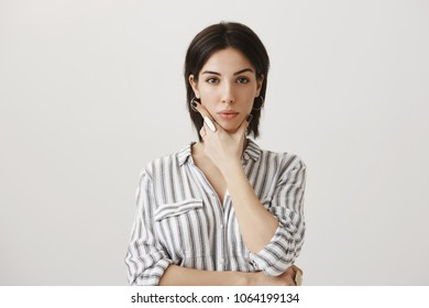 Serious and attractive european girl trying to concentrate while making up new concept for her design, standing over gray background with strict and focused expression, holding hand on jaw, planning