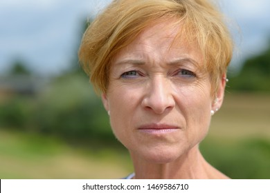 Serious attractive middle-aged woman staring earnestly at the camera in a close up cropped head shot portrait outdoors