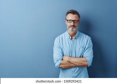 Serious authoritative bearded middle-aged man with folded arms standing staring intently at the camera against a blue studio background with copy space