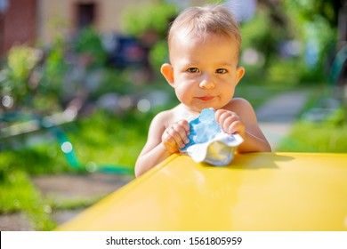 serious baby holds and eating fruit puree in pouch and looking into the camera in front of the yellow table. on the background is  a green garden on a sunny day in blur