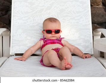 Serious baby on beach in bikini