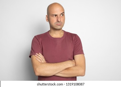 Serious bald man looking aside with suspicion. Isolated on grey studio background