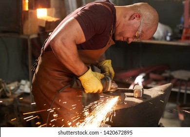 Serious bald young blacksmith in apron and gloves standing at anvil and polishing metal piece with grinder