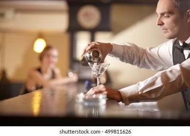 Serious bartender preparing cocktail in empty bar