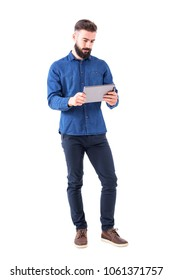 Serious bearded business man holding and watching tablet in both hands. Full body isolated on white background.
