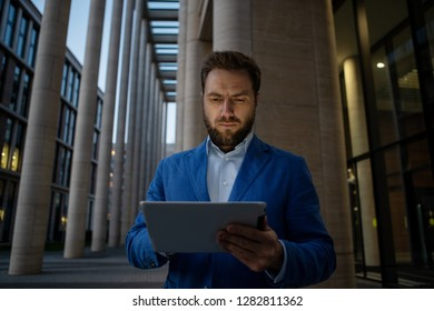 Serious bearded businessman in suit using touchpad on street with modern building in twilight