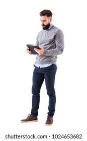 Serious bearded businessman or teacher reading notebook paper. Full body length portrait isolated on white studio background.