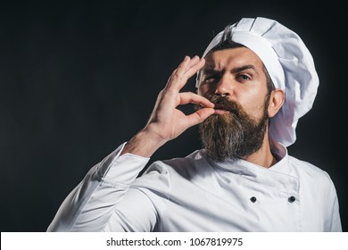 Serious bearded chef, cook or baker gesturing excellent. Male chef in white uniform with perfect sign. Professional chef man showing sign for delicious. Cook with taste approval gesture. Copy space.