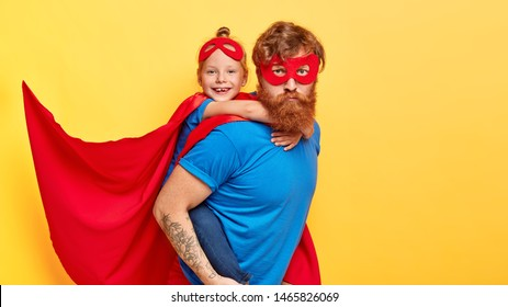 Serious bearded ginger father superhero carries small female kid on back, do good things together, wear costumes with cape, ready for children party, isolated on yellow wall. We are strong heroes