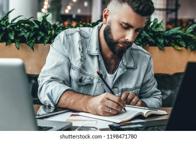 Serious bearded hipster man sitting in office at desk, making notes in notebook, working on laptop.Entrepreneur analyzes information, develops business plan.Freelancer works in cafe. Student learning.