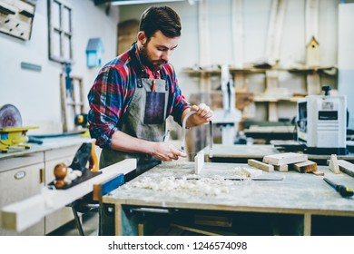 Serious bearded male joiner making details by himself using sharp tools for timber on working space, concentrated foreman in apron repairing wooden staff with instruments in workshop with sawdust
