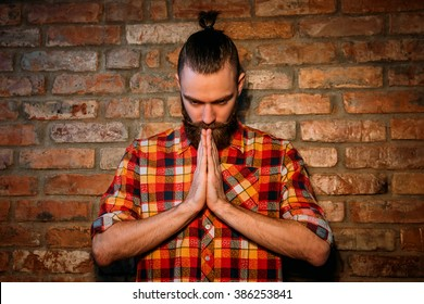 Serious bearded man meditates on a background of a brick wall