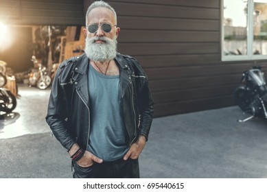 Serious bearded old man wearing leather