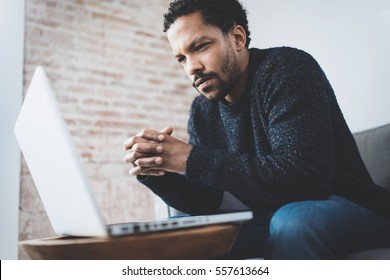 Serious bearded young African man thinking while sitting on sofa at his modern coworking place.Concept of business people using mobile devices.Blurred background