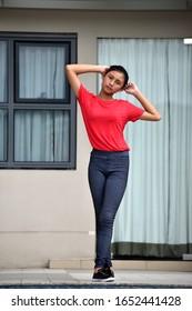 Serious Beautiful Asian Girl Standing By Condo