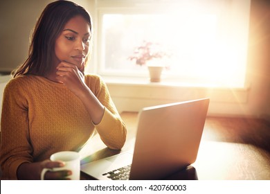 Serious beautiful woman with hand on chin sitting near bright window while looking at open laptop computer on table and holding white mug