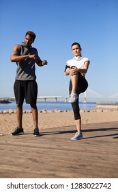 Serious beautiful young multi-ethnic couple doing warmup on beach: lady stretching leg while black guy twisting upper body outdoors