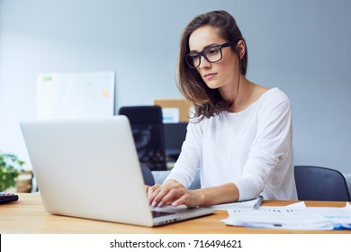 Serious beautiful young woman typing on laptop in a bright modern office