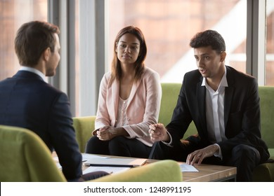 Serious biracial businesswoman and middle eastern ethnicity business partners listening caucasian businessman sitting in comfortable couches negotiating discussing startup new project in modern office