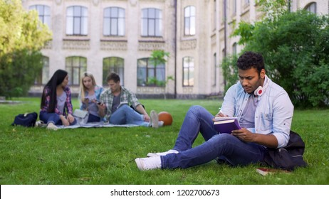 Serious biracial male student sitting on grass and writing essay, doing homework