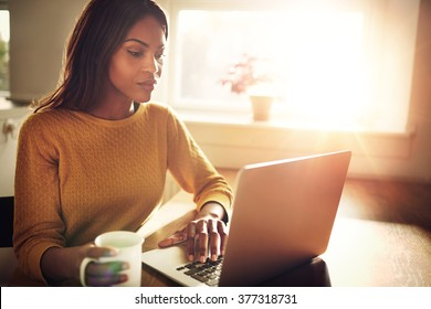 Serious Black adult single female sitting at table holding coffee cup and typing on laptop with light flare coming through window