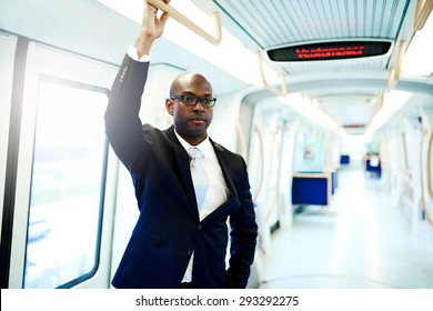 Serious Black American Businessman Commuting on a Subway Train and Holding on an Overhead Railing