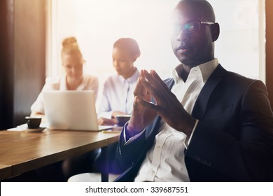 Serious black business man sitting in front of his employees at office