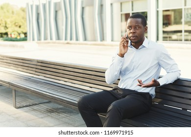 Serious black businessman having tough conversation on smartphone outdoors. Young african-american salesman talking with client near business centre on the bench in urban area cityscape