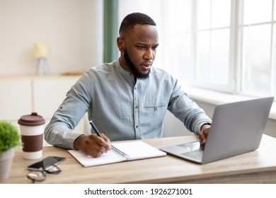 Serious Black Businessman Working Taking Notes And Using Laptop Computer Writing Business Report At Workplace In Modern Office. Entrepreneurship Occupation And Business Career