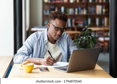 Serious black guy taking notes while studying online in front of laptop at city cafe