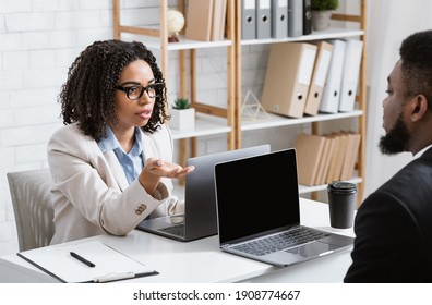 Serious black woman speaking to her male colleague at company office, asking about common project, copy space. Teamwork and cooperation at workplace concept
