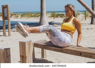 Serious blond woman wearing sportive clothes and doing twists with legs training abdomen while sitting on wooden bench on beach.