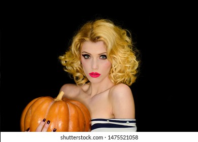 Serious blonde girl with pumpkin. 31 October. Halloween. Trick or treating. Halloween party. Happy Halloween. Sexy woman in witch halloween costume. 31 October. Holidays, decoration and party concept.