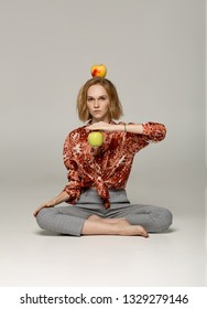 Serious blonde girl in trendy red shirt sitting in yoga position holding apple in hand, second apple is on her head, healthy food concept, studio photo on gray background