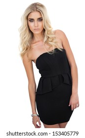 Serious blonde model in black dress posing looking at camera on white background