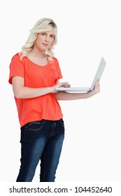 Serious blonde woman holding a laptop in her left hand against a white background