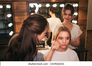 Serious blonde woman sit on chair in beauty room. Make up artist put some color on brows. Hairdresser sstand behind and lift hair up. She smile.