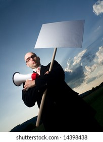 Serious bold man in glasses and black suit, holding sign and megaphone. Space for text is available.