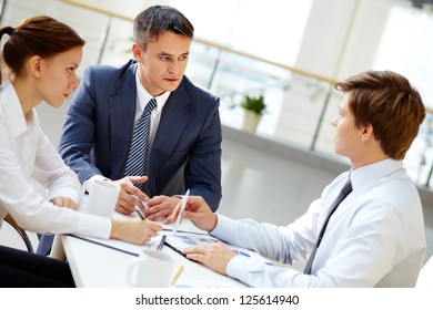 Serious boss looking at one of his employees and listening to him at meeting