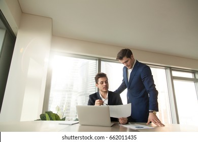 Serious boss talking to employee at workplace, discussing document, reporting on project, showing presentation, demonstrating task results, team leader checking work of subordinate manager